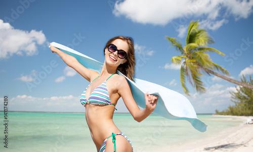 woman in bikini and sunglasses with towel on beach