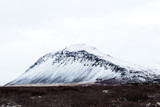 Snow covered mountain range with high contrast black volcanic rock.