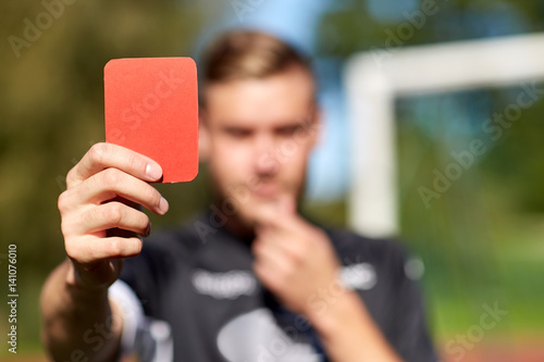 Plexiglas Voetbal referee hands with red card on football field