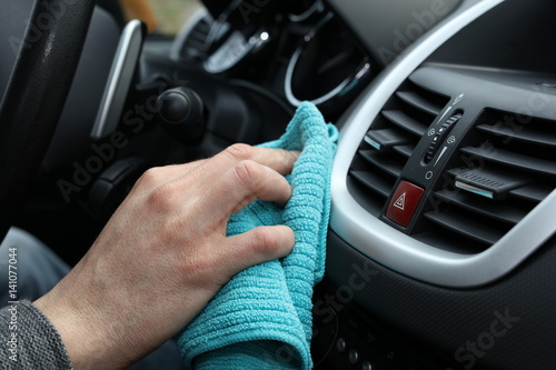 Hand with microfiber cloth cleaningcar interior close up