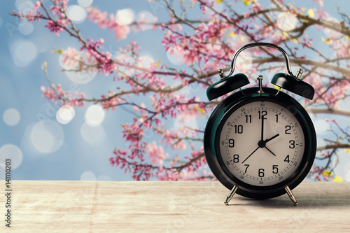 Spring time change concept with alarm clock on wooden table over nature tree blossom background