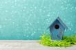 Spring season concept with bird house over bokeh background