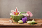 Spa and wellness concept with flowers in bowls and candles on wooden table over rustic background