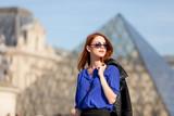 beautiful young woman walking near the Louvre