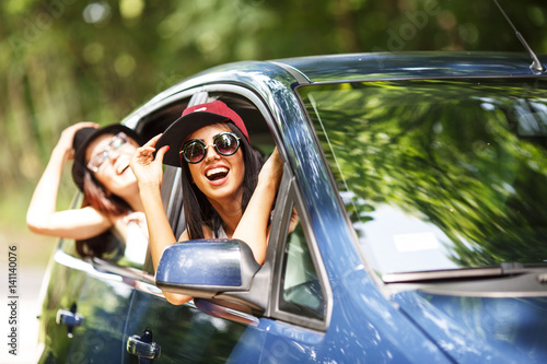 Two young women on car trip.They are travel with car and making fun.Looking through window.
