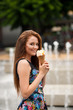 Young woman with ice cream in city on hot late summer afternoon