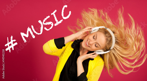 Beautiful young woman in black and yellow vibrant dress dances as she listens to the music over pink background