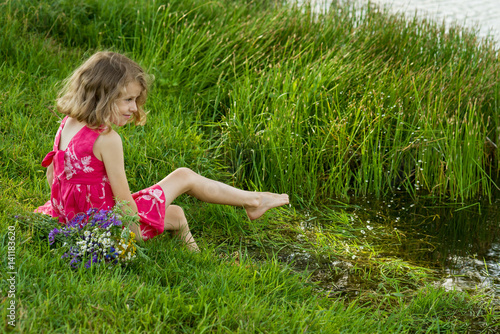 Little girl is sitting on the lake shore Poster