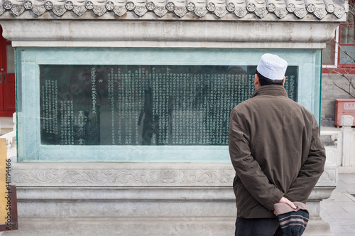 Poster Man reads an inscription on an ancient stele at Niujie Mosque, Beijing, China