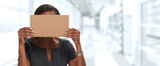 Business woman hiding face with cardboard.