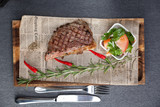 Beef steak on the grill with a salad of red tomatoes on wooden plate