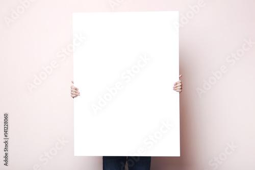 Mężczyzna mienia pusty plakat na beżowym tle