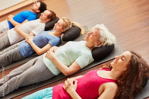 Seniorin in Gruppe bei Meditation