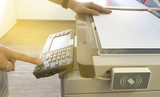 Man copying paper from Photocopier with access control for scanning key card sunlight from window - 141247226