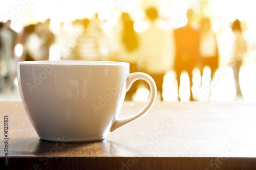 Hot coffee in white cup on wooden table in rush hour morning. Abstract blur people walking in rush hour urban life.