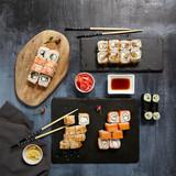 Japanese Sushi - Set of Maki Sushi Roll, Soy Sauce and Ginger over Stone Background
