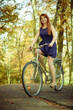 Redhead lady cycling in park.