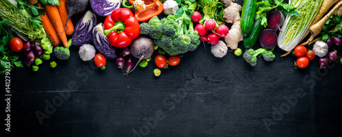 Wall mural Big set organic food. Fresh raw vegetables. On a black chalkboard.