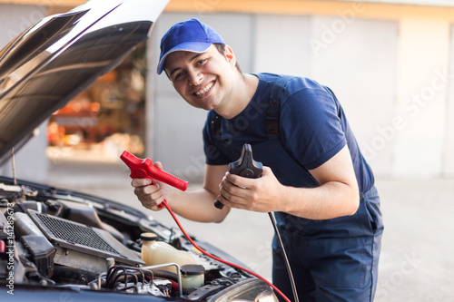 Mechanic using cables to start a car engine