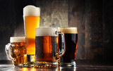 Four glassed of beer on wooden background - 141298273