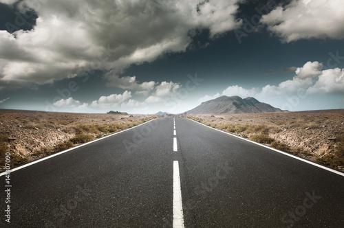 Straße führt durch abgelegende Landschaft Poster