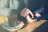 Woman using mobile phone and drinking hot chocolate in cafe