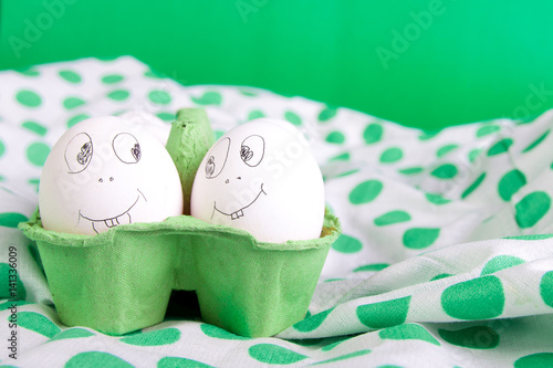 Easter eggs with funny faces in the green box on polka dot tablecloth Poster