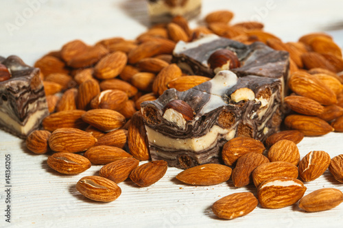 Póster candy paste and almonds on white wooden background