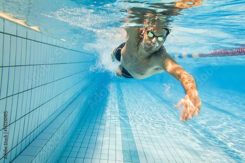 Freestyle swimmer underwater in swimming lane