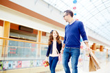 Father and daughter walking down shopping center and talking