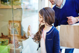 Cute child looking at shop-display with her father near by