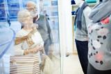 Seniors paying attention to new collection of clothes in department store