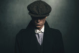Mysterious portrait of retro 1920s english gangster with flat cap. - 141377601