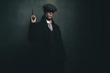 Dangerous retro 1920s english gangster standing with gun. - 141377605