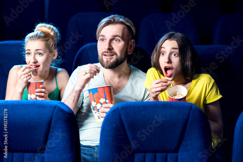 Scared friends watching film sitting together with popcorn in the cinema