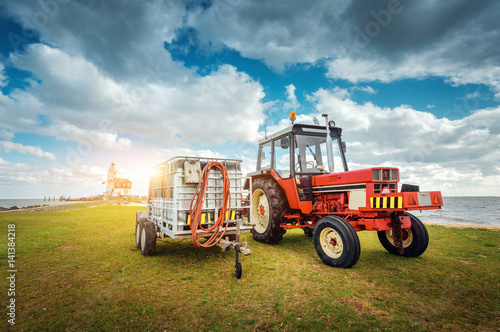 Poster Red tractor with trailer on the grass field against lighthouse and blue cloudy sky in spring at sunset