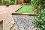 Fototapety A section of a residntial garden, yard with wooden decking, patio over a fish pond, a section of artificial grass and an area of stone pebble. There is a bamboo plant and a dog in the garden.