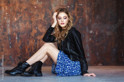Beautiful young girl in a black jacket. Fashion portrait  on a brown background