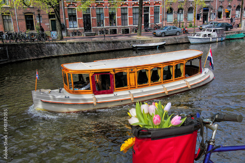 Poster Famous Amsterdam with basket of colorful tulips against boat in Holland