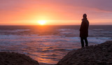 Silhouette of a woman observing sunset the on a deserted beach in Texel, The Netherlands.
