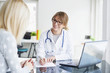 canvas print picture - Doctor and her patient. Shot of a middle aged female doctor sitting in front of laptop and consulting with her patient.