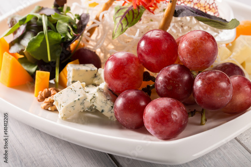 Póster Restaurant cheese plate - various types of cheeses with grapes and walnut on white plate