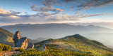 Panoramic landscape in the mountains at sunrise. Dramatic sky with colorful clouds.