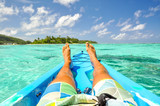 Stunning view of a young man's legs in a kayak near Motu Koromiri, a small island in the lagoon of Rarotonga near Muri Beach. Cook Islands in the South Pacific Ocean, Clear, shallow water, palm trees. - 141425472