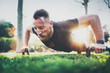 Fitness lifestyle concept.Muscular athlete exercising push up outside in sunny park. Fit shirtless male fitness model in crossfit exercise outdoors.Sport fitness man doing push-ups.Blurred background.