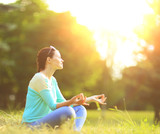 Attractive young woman in lotus position in the park