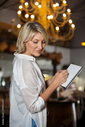 Female costumer maintain record in notepad