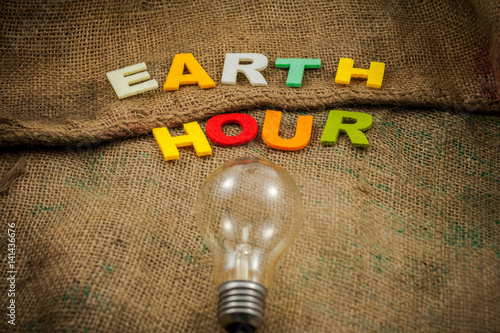 Bulb light and alphabet over the sackcloth sorting EARTH HOUR