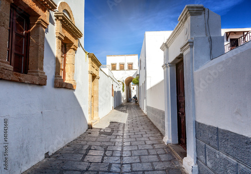 A street with white buildings in the old Greek city of Lindos on the island of Rhodes. A popular destination for vacations and holidays