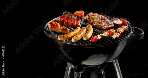 Variety of meat grilling on a portable barbecue